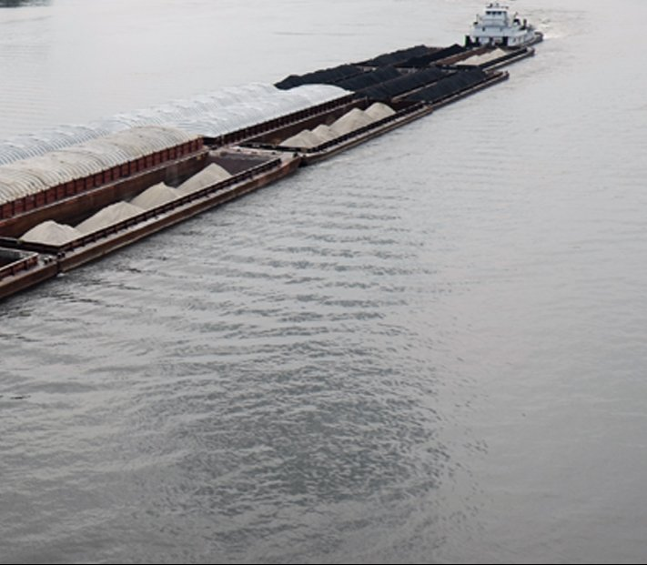 A massive barge moving down the Ohio River